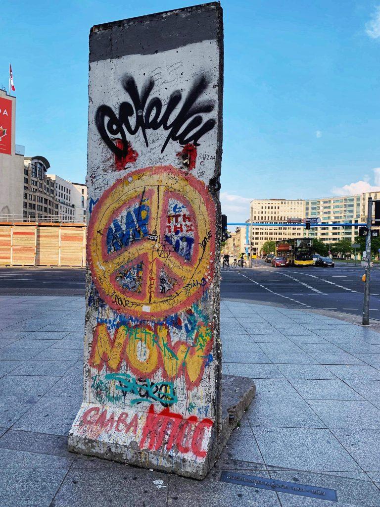 Rest av Berlinmuren. Tagget med ulige fager og et stort fremhevet gult fredstegn.