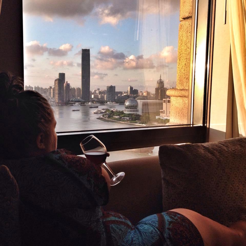 Kvinne som sitter i vinduskarmen og ser ut på skyskrapere langs elva