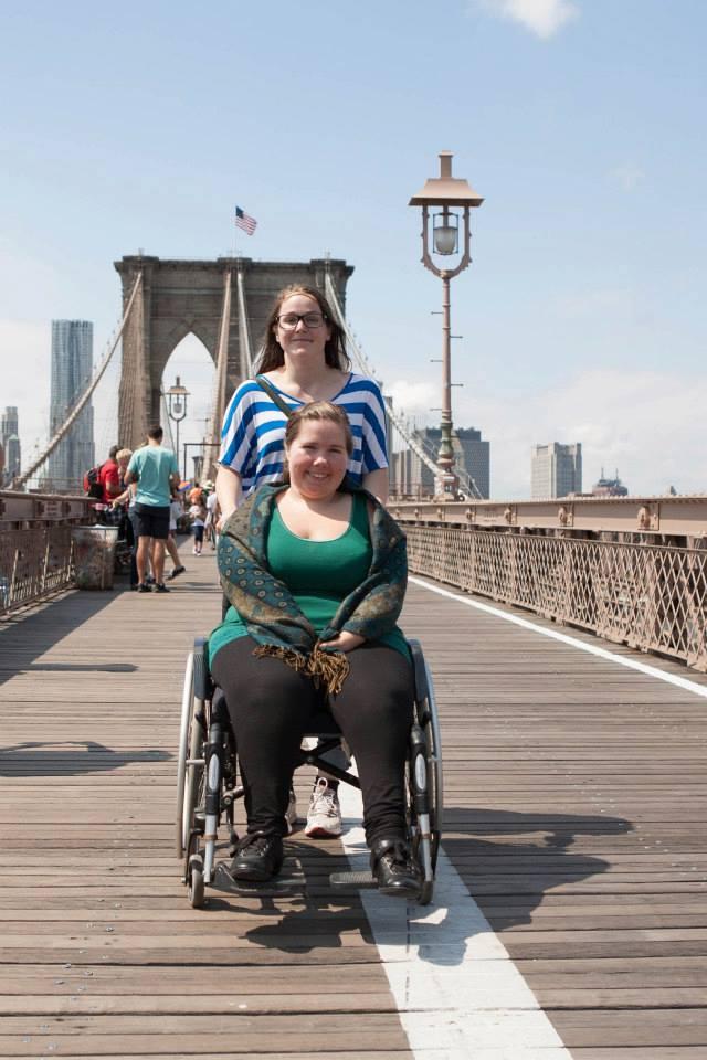 To kvinner på Brooklyn Bridge, den ene i rullestol ikledd grønn singlett og sjal og den andr stående bak i stripete t-skjorte.