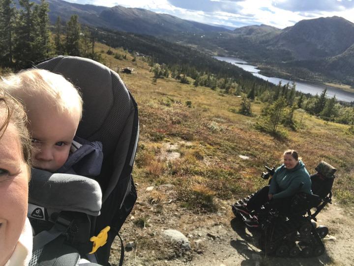 Selfie hvor du ser halve ansiktet til en kinne med en liten gutt i bæresele på ryggen. Bak de en kvinne i belterullestol og god utsikt over fjellandskap helt ned til vannet nederst i dalen.