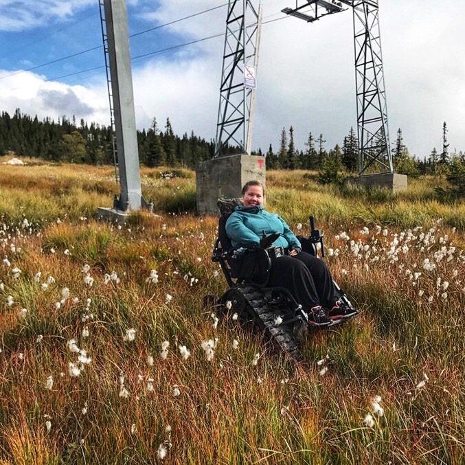 Smilende kvinne i lette fleece-turklær sittende i en belterullestol blant høyt gress ved foten av skiheisen.