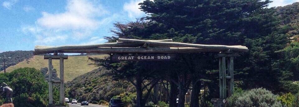 """Veiportal av trebjelker med skiltet """"Great Ocean Road"""" hengende over veien."""