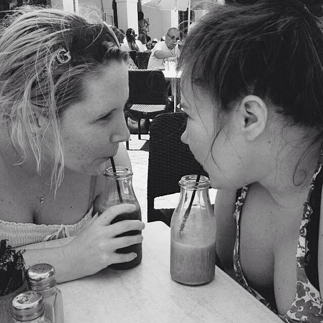 To jenter drikker milkshake fra små glassflasker med sugerør