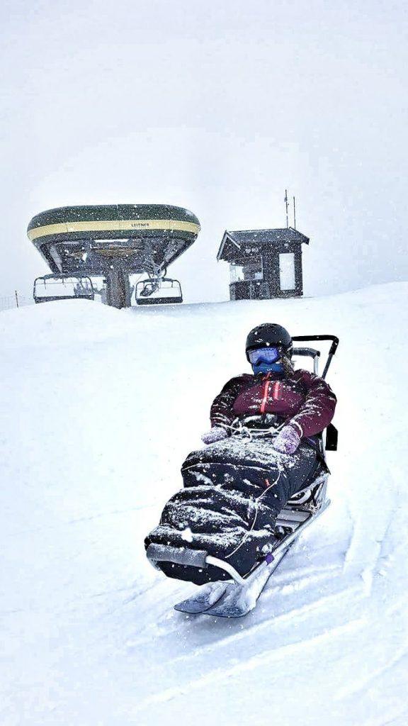 En snødekket Lena i biski. I bakgrunnen ser man toppen av skiheisen og tett snøvær.