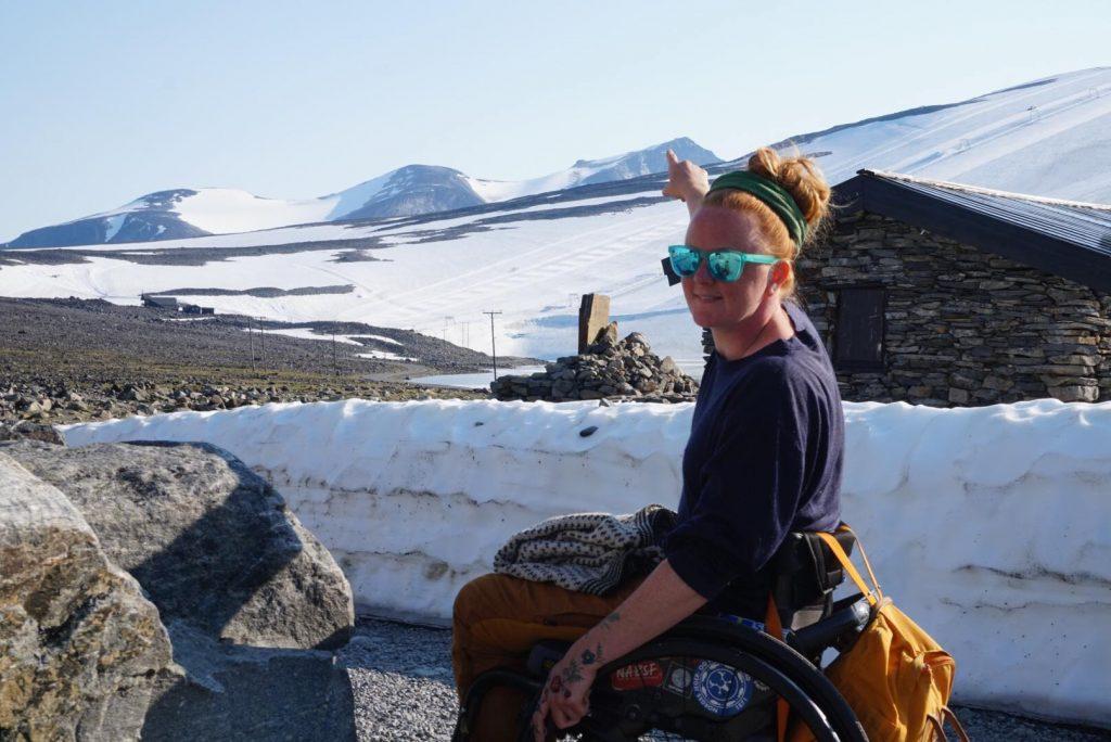 Kvinne i manuell rullestol peker opp på en snødekt fjelltopp.