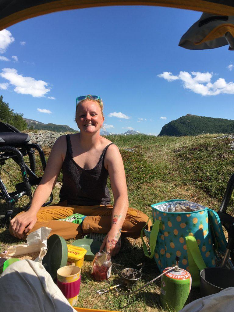 Smilende kvinne sittende på bakken utenfor teltet sitt med masse mat og utstyr foran seg. Blå himmel og sol!