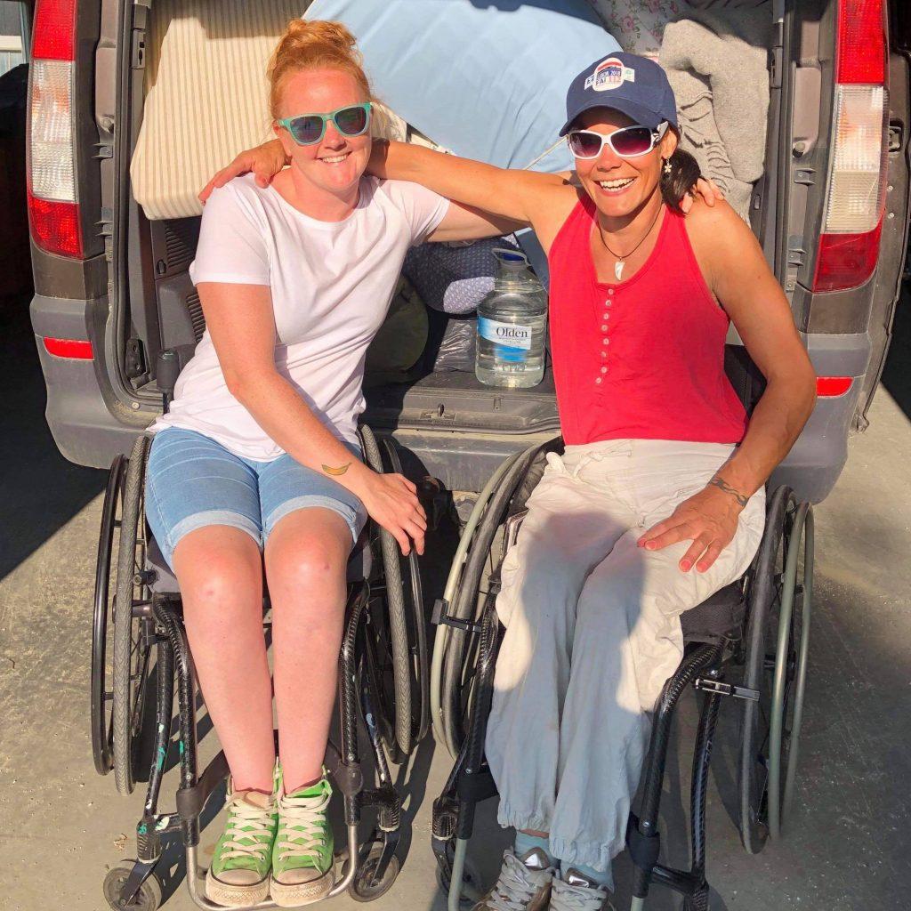 To smilende kvinner i manuell rullestol foran et fullpakka bagasjerom.