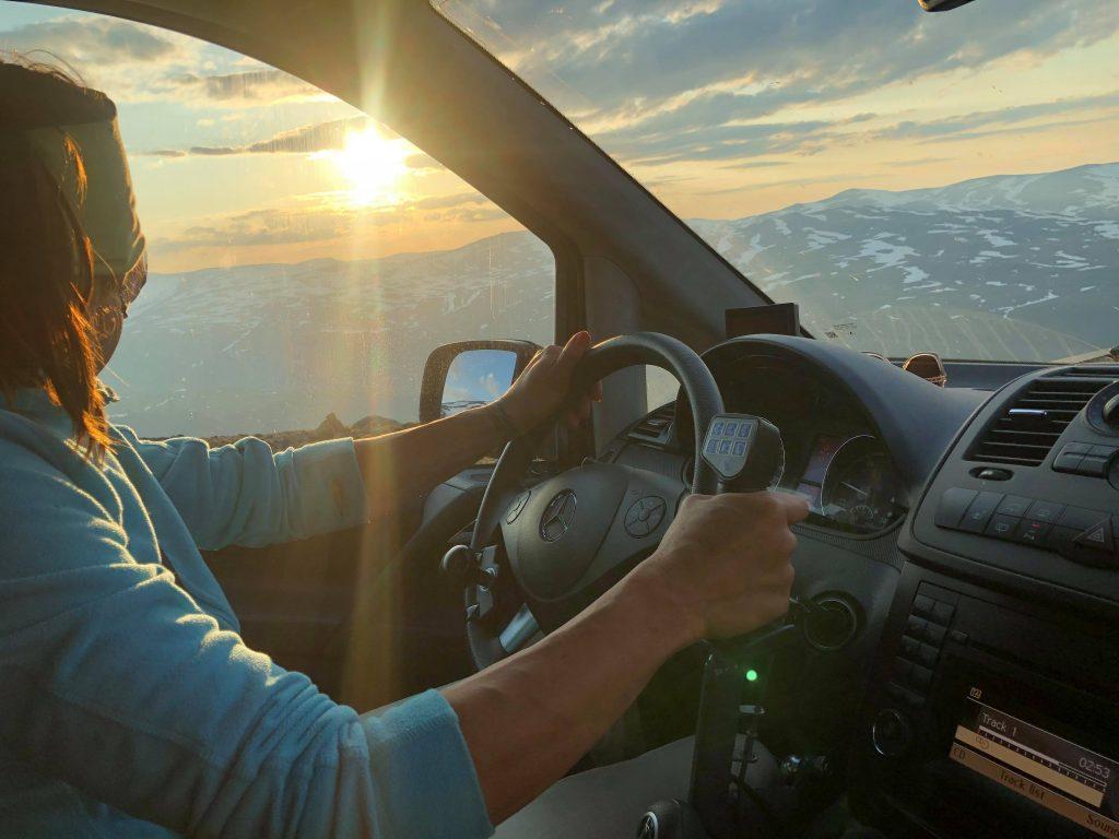 Kvinne som kjører bil. I bakgrunnen ser vi delvis snødekt fjellandskap.