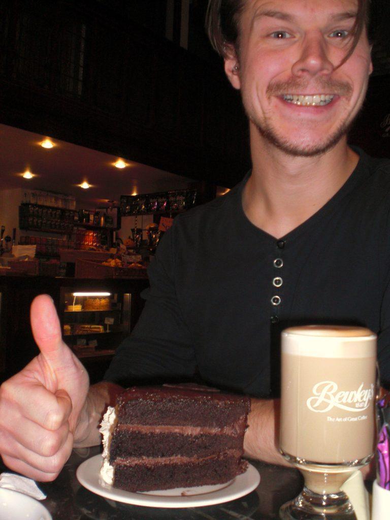 Eivind poserer med et deilig stykke sjokoladekake og kaffe på kafé