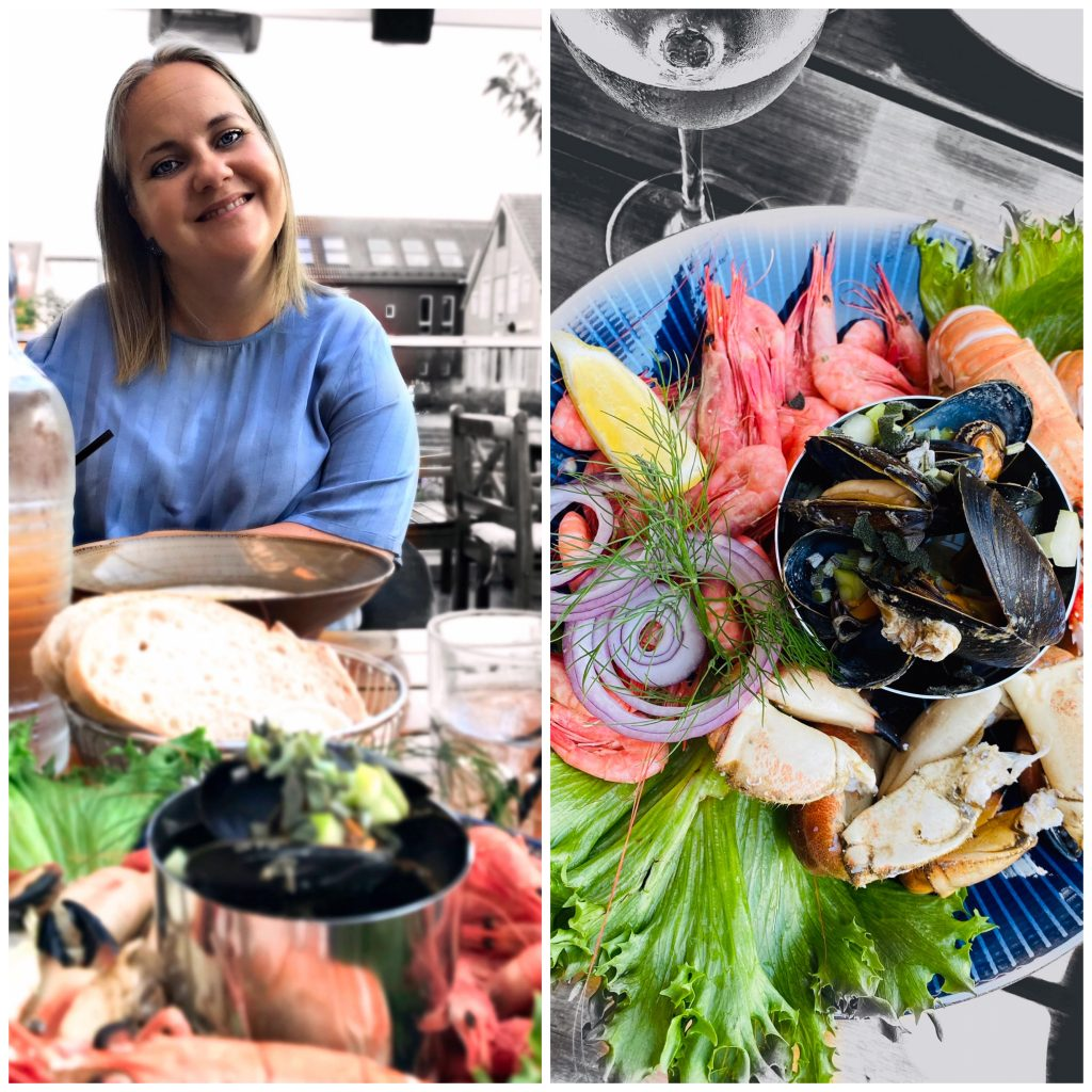 Anne poserer med en skål fiskesuppe og en overfylt skalldyrs-tallerken