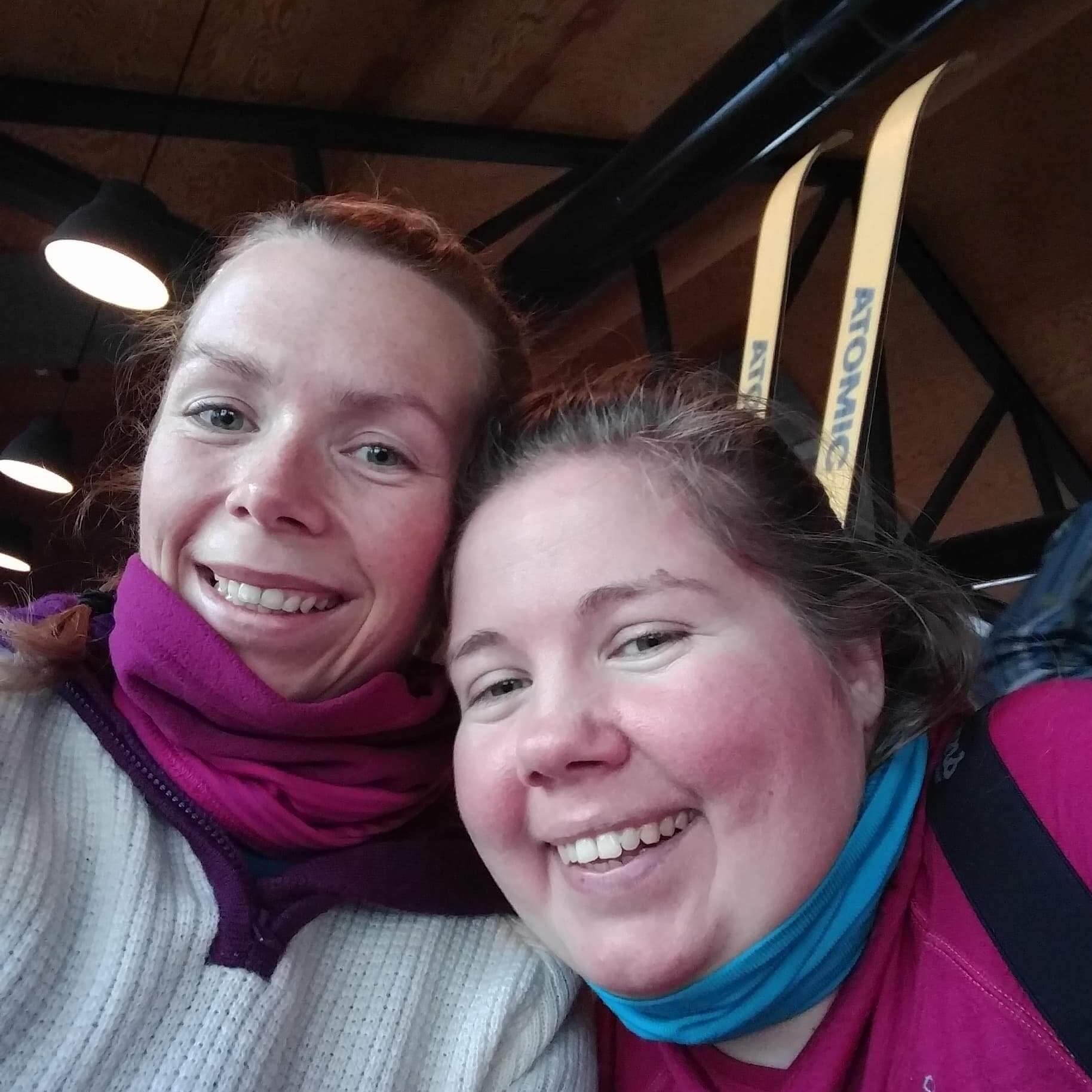 Selfie av to Lin og Lena i ullklær. I bakgrunnen ser vi et tretak og to skitupper som stikker opp.
