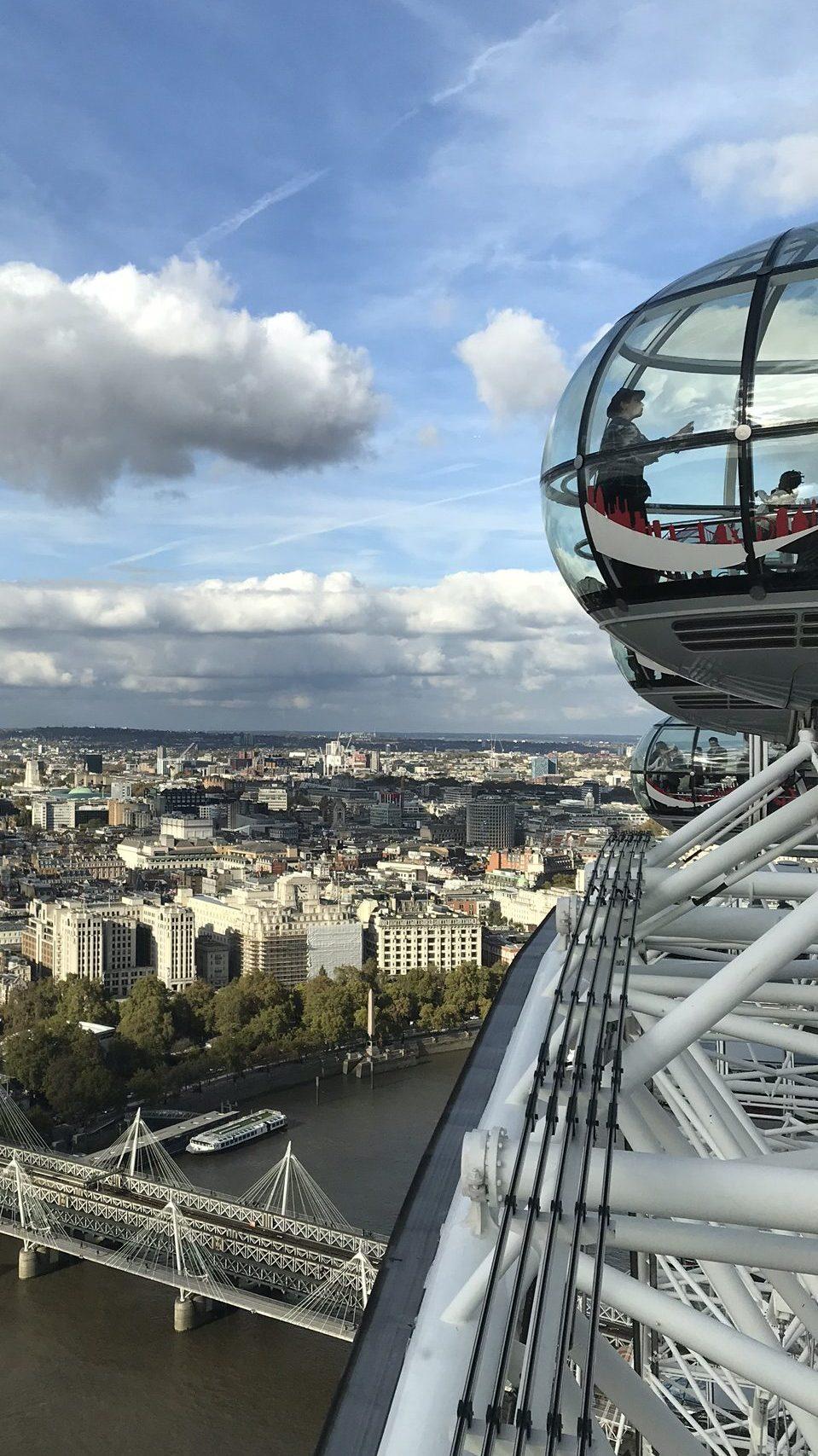 Bilde fra toppen av London Eye hvor man ser halve nabokuben, blå himmel og overblikk av London by.