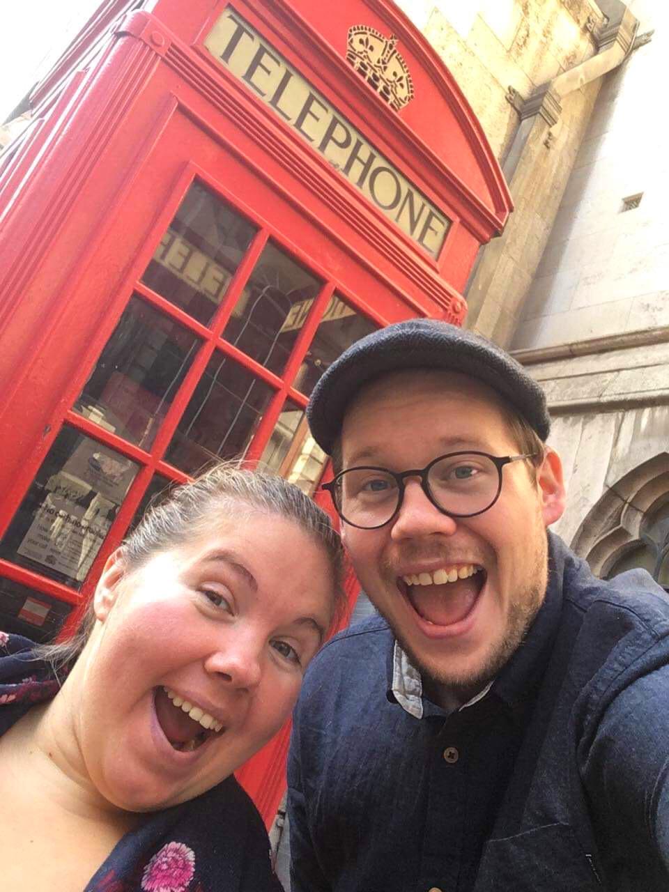 Lena og Bent tar selfie foran en rød telefonboks.