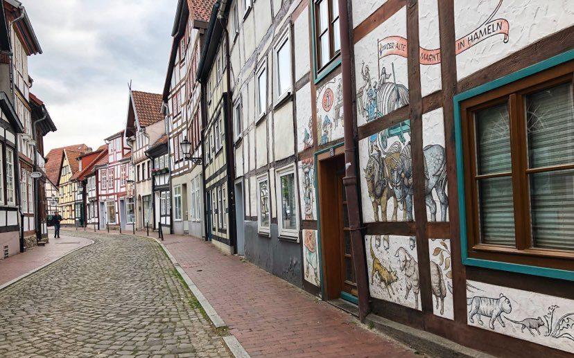 Stemningsbilde langs en av gatene funne av små bindeverkshus. Det fremste har nydelige veggaleri på veggen.