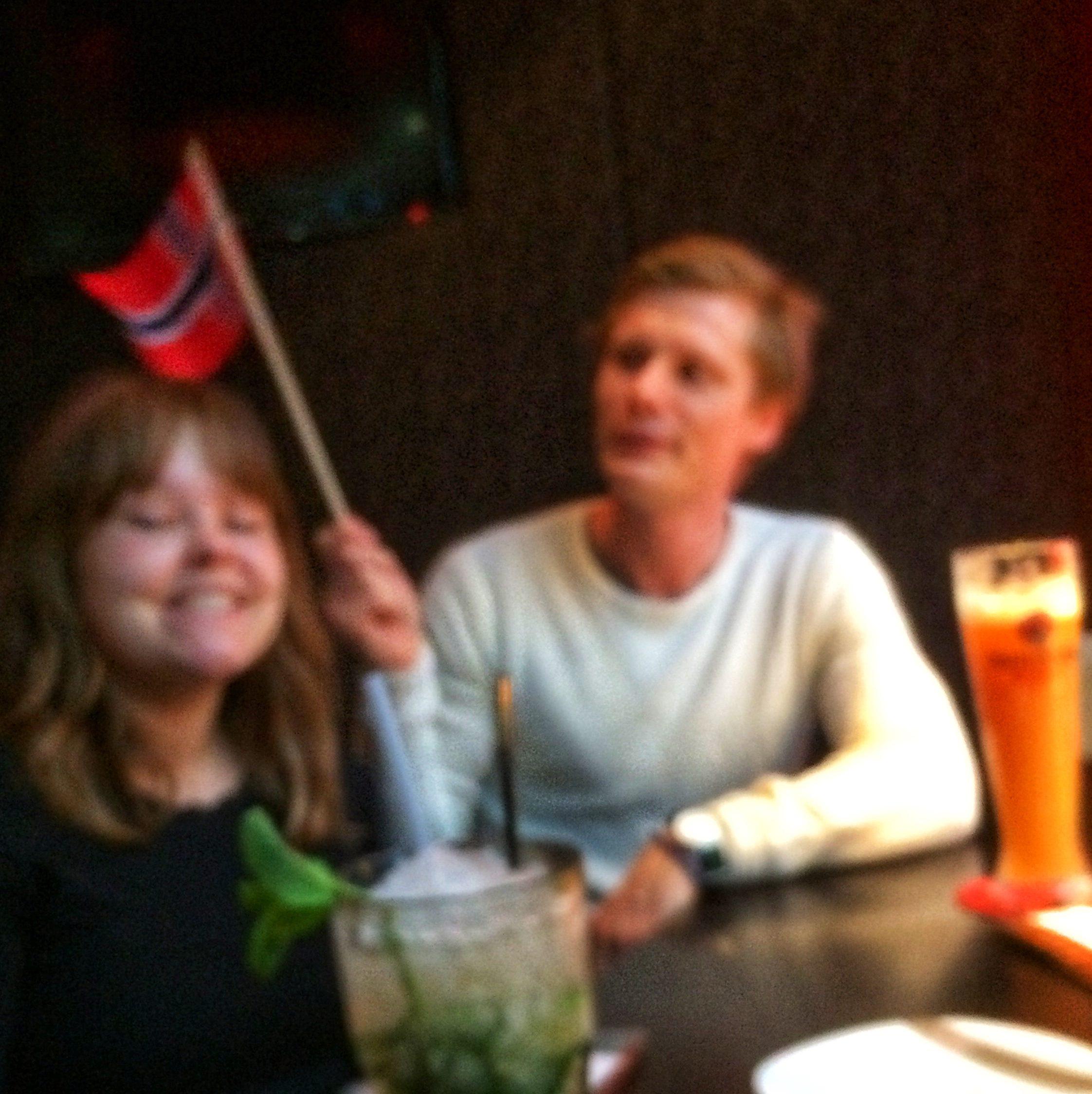 Et slørete bilde av en kvinne og en mann på bar som vaier med et typisk norsk 17.mai-flagg i bakgrunnen.