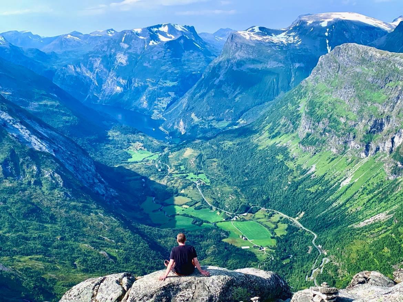 En mann sitter på en steinhylle ut mot fjellkanten. Utsikt ned mot Geirangerfjorden.