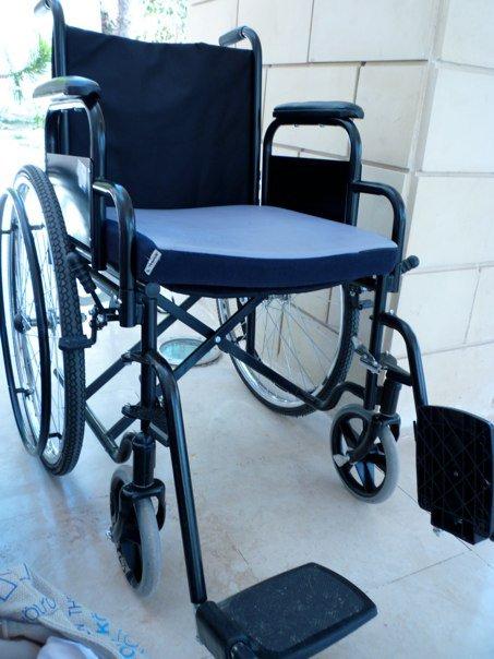 Rullestol av tung og knotete modell. Ligner typiske rullestoler fra flyplasser og sykehjem.