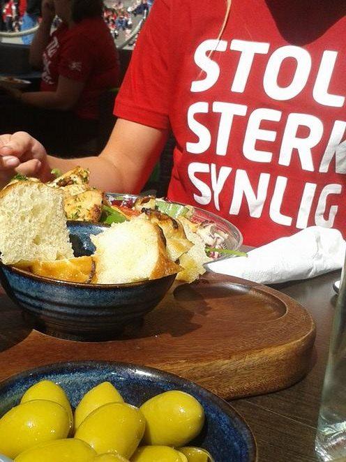 """Bilde av et tapasbord på restaurant. Ved bordet ser man ei jente med den røde """"Stolt, sterk, synlig""""-t-skjorten"""