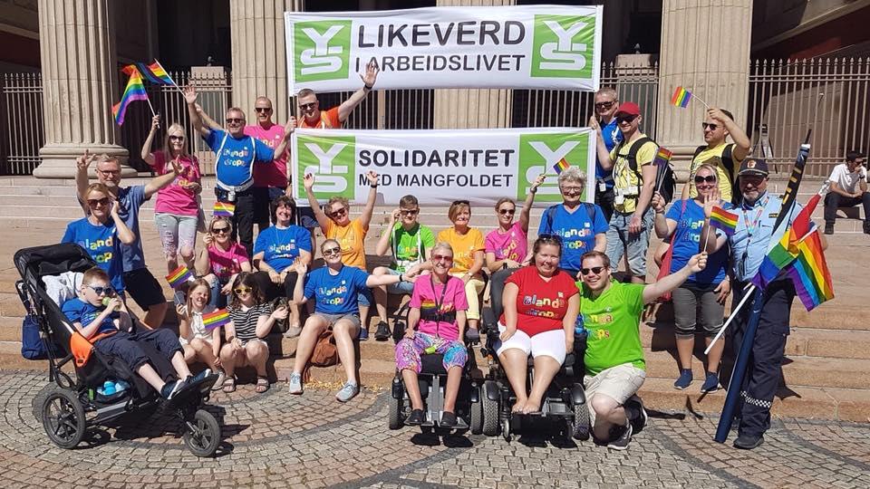 """YS' Pride-gruppe oppstilt foran fanene """"YS Likeverd i arbeidslivet"""" og YS Solidaritet med mangfoldet"""". Gående, rullende og vinkende med fargerike t-skjorter med teksten """"Blanda drops"""""""
