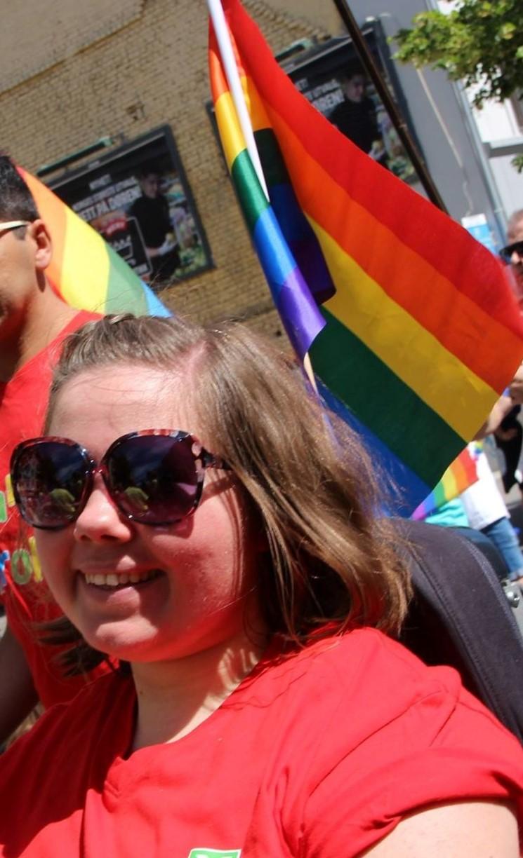 Kvinne med solbriller og vaiende pride-flagg bak seg